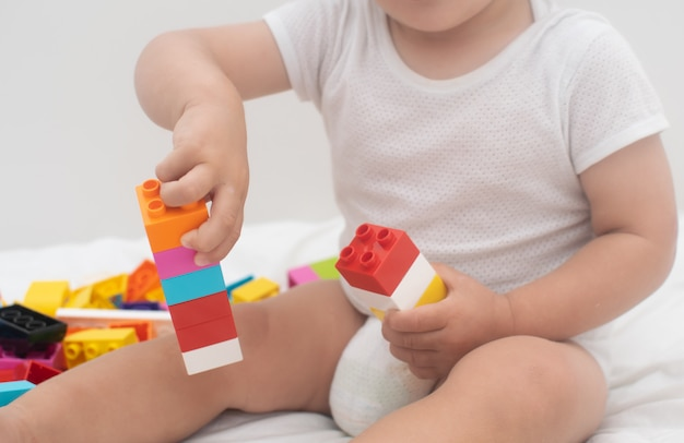 Mały chłopiec bawi się kolorowy blok na białym łóżku