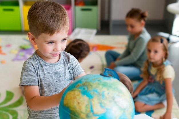 Mały chłopiec bawi się kulą ziemską