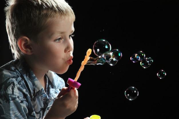 Mały chłopiec bawi się kulkami mydlanymi