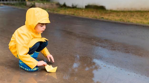Mały chłopiec bawi się łodzią papieru z miejsca na kopię