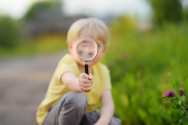 Mały chłopiec bawi się lupą.