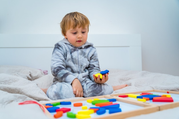 Mały chłopiec bawi się na łóżku w drewnianym konstruktorze magnetycznym