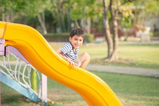 Mały chłopiec bawi się na placu zabaw na świeżym powietrzu