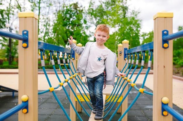 Mały chłopiec bawi się na placu zabaw.