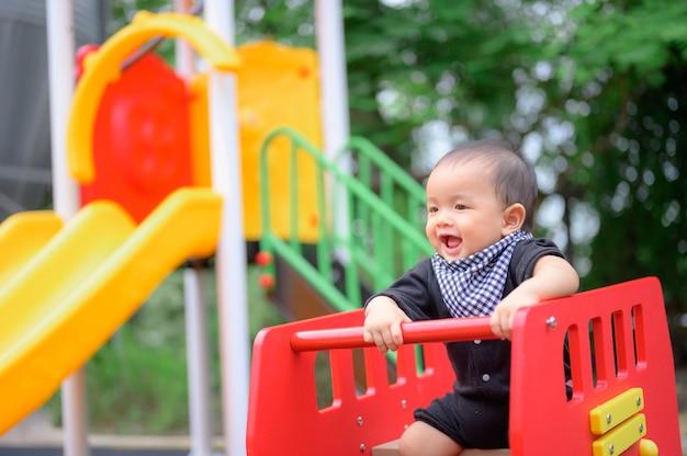 Mały chłopiec bawi się na placu zabaw