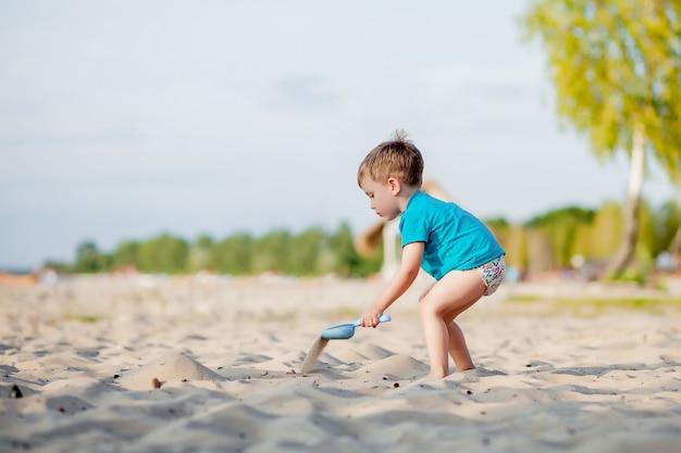 Mały chłopiec bawi się na plaży swoją plastikową łopatą