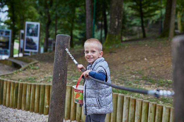 Mały chłopiec bawi się na poziomych prętach na placu zabaw