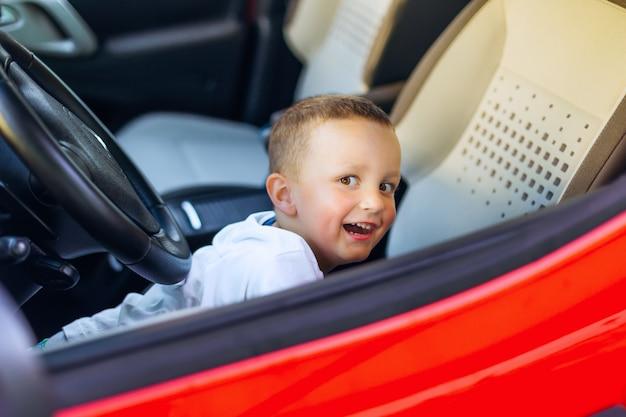 Mały chłopiec bawi się na przednim siedzeniu czerwonego samochodu i uśmiecha się szczerze