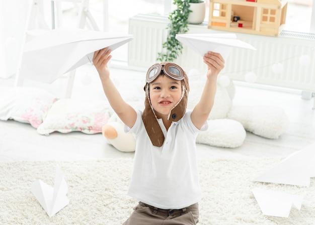 Mały chłopiec bawi się papierowymi samolotami