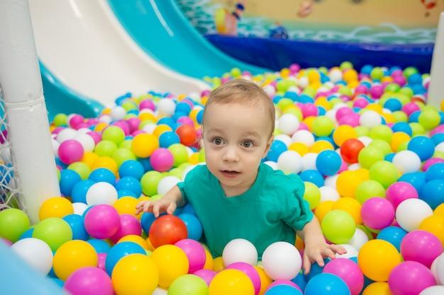 Mały chłopiec bawi się piłkami