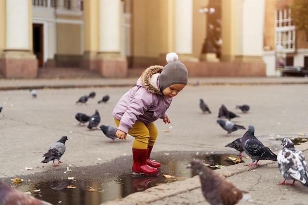 Mały chłopiec bawi się w kałuże, plac miasta z ptakami. gołębie jesienne dzieciństwo