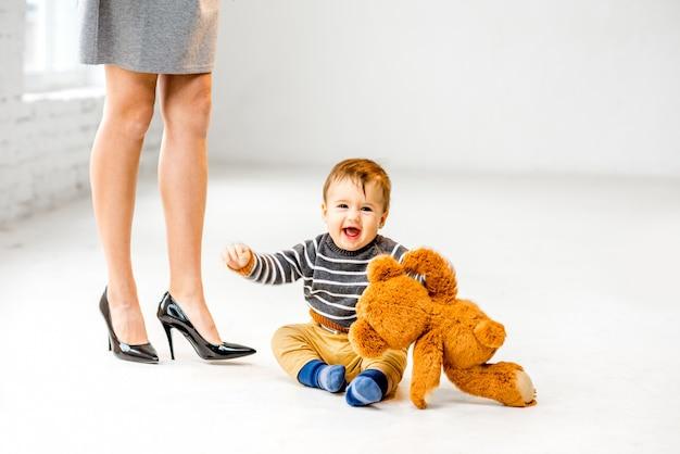 Mały chłopiec bawi się w pobliżu pięknych nóg kobiety na białej podłodze