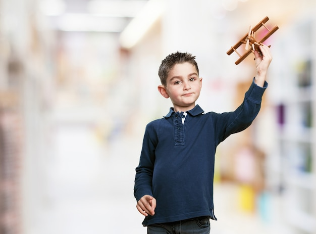 Mały chłopiec bawi się z drewnianego samolotu