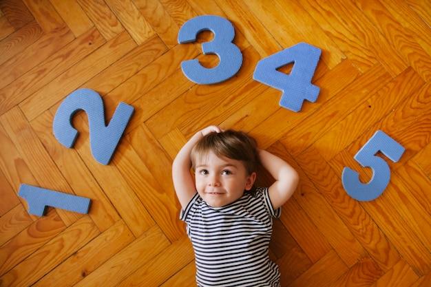 Mały chłopiec bawi się z numerami