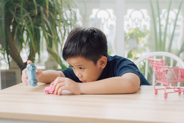 Mały chłopiec bawi się zabawką samochodową na stole