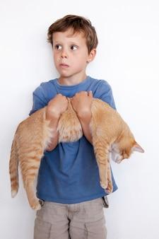 Mały chłopiec bawi się ze swoim kotkiem, niosąc go ze sobą - na białym tle. ładny chłopiec niesie pięknego kota.