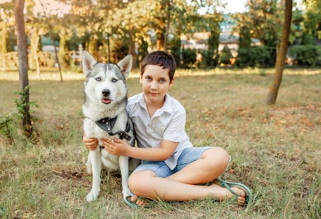Mały chłopiec bawi się ze swoim pięknym psem na zewnątrz, ciesząc się razem
