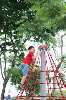 Mały chłopiec bawiący się na drabinkach na placu zabaw