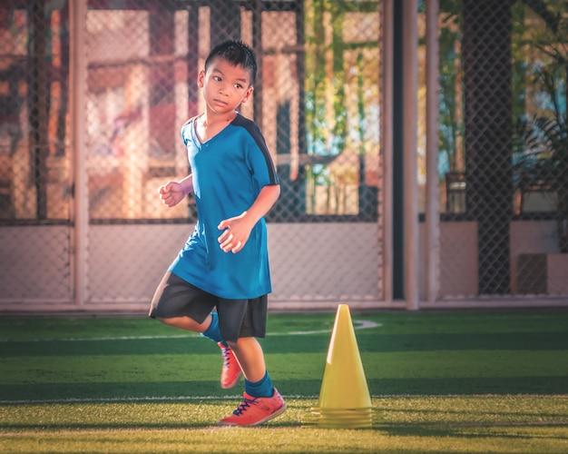Mały chłopiec biegnie między treningiem sportowym w sesji treningowej piłki nożnej