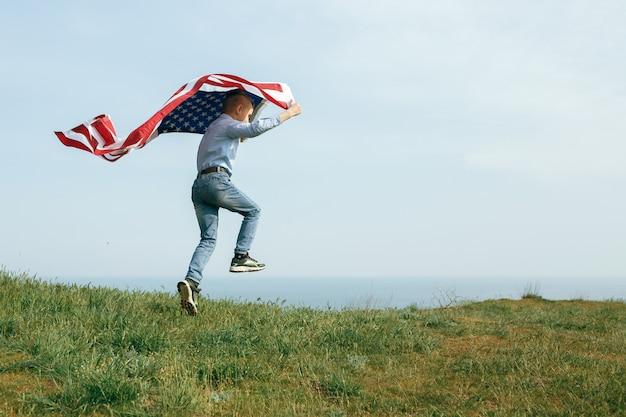 Mały chłopiec biegnie z flagą stanów zjednoczonych. dzień niepodległości 4 lipca.