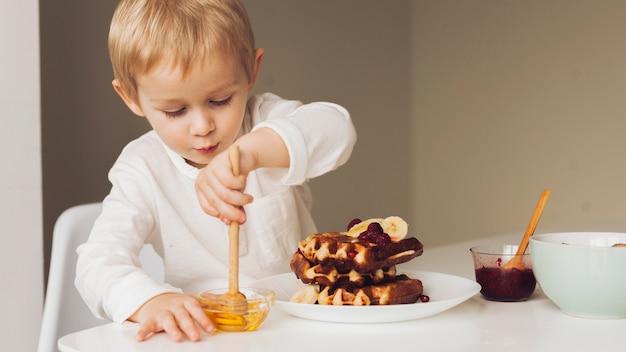 Mały chłopiec biorąc miód