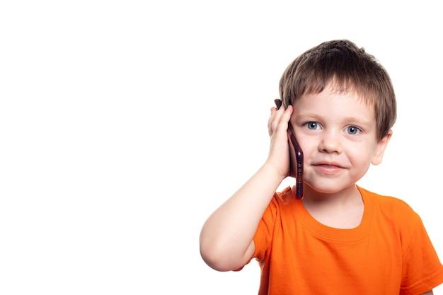 Mały chłopiec brunet rozmawia przez telefon