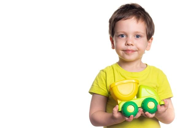 Mały chłopiec brunet trzymając zabawkę w rękach