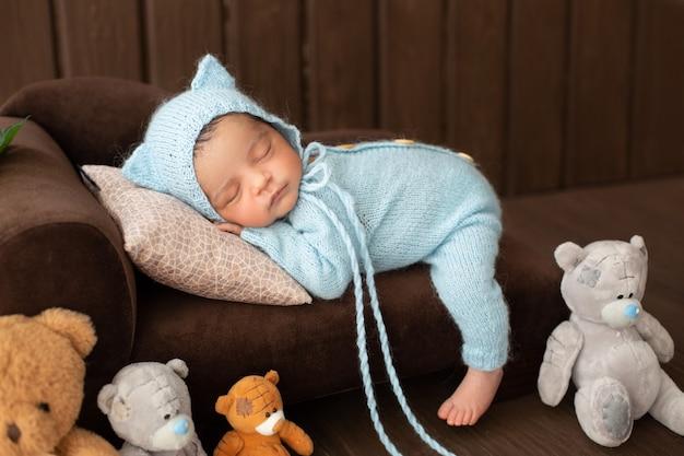 Mały chłopiec całkiem noworodek r. na brązowej kanapie w niebieskim szydełkowanym pijama otoczony zabawkami