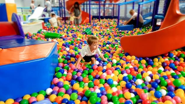 Mały chłopiec chodzi i wspina się po wielu kolorowych plastikowych piłeczkach na placu zabaw w centrum handlowym