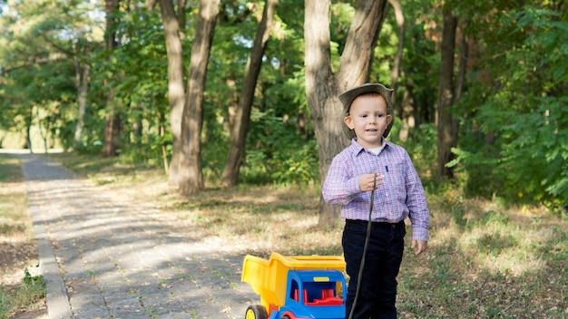 Mały chłopiec ciągnie zabawkową ciężarówkę po wybrukowanej wiejskiej drodze w lesie