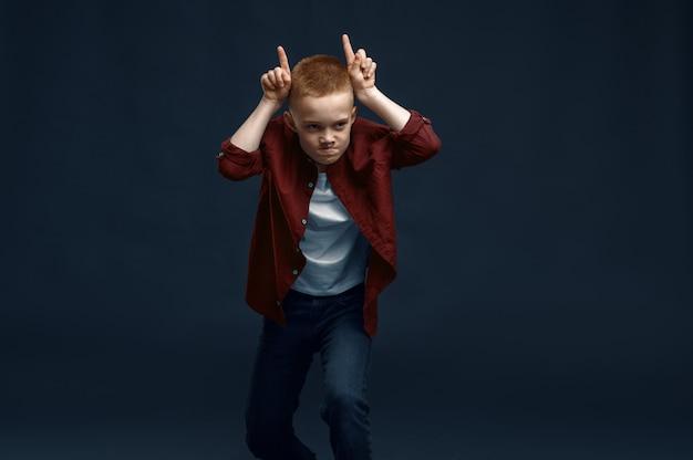 Mały chłopiec co twarz w studio. szczęśliwe dzieciństwo, dzieci, zabawy, zabawne dziecko na białym tle na ciemnym tle, emocje dziecka
