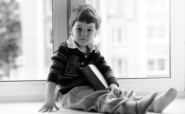 Mały chłopiec czyta książkę. dziecko siada przy oknie i przygotowuje się do lekcji. chłopiec z książką w rękach siedzi na parapecie.