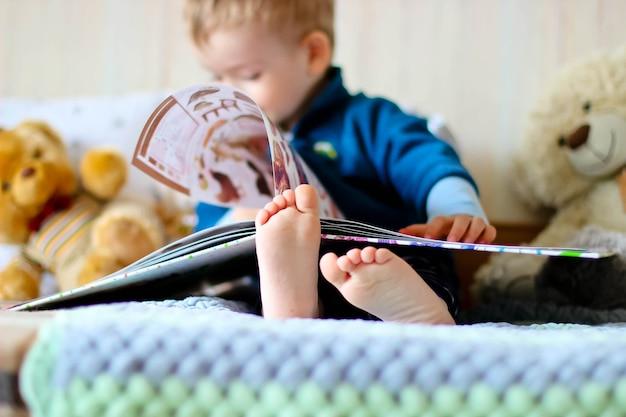 Mały chłopiec czyta książkę z misiami na dzianinowej kracie