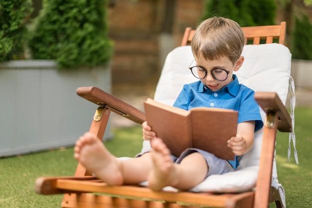 Mały chłopiec czyta siedząc na zewnątrz