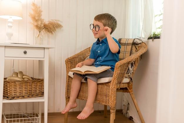 Mały chłopiec czyta siedząc w fotelu