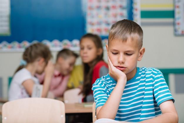 Mały chłopiec czytania podręczników w klasie