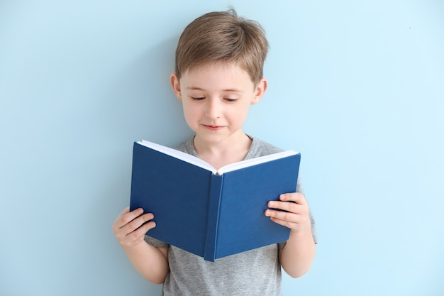 Mały chłopiec czytanie książki na powierzchni koloru