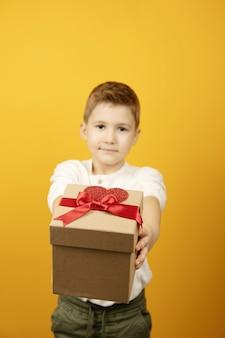 Mały chłopiec dając pudełko z czerwoną wstążką i kształt serca na białym tle, podając prezent dla dziecka. selektywne focus, skupienie się na pudełku prezentowym, rozmyte tło.