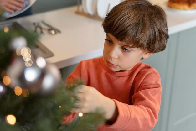 Mały chłopiec dekorujący choinkę
