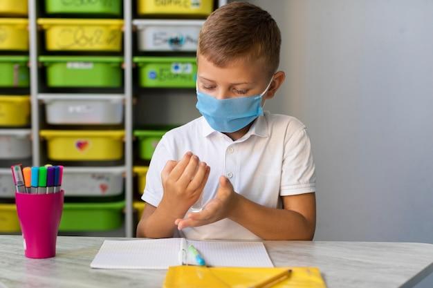 Mały chłopiec dezynfekuje ręce