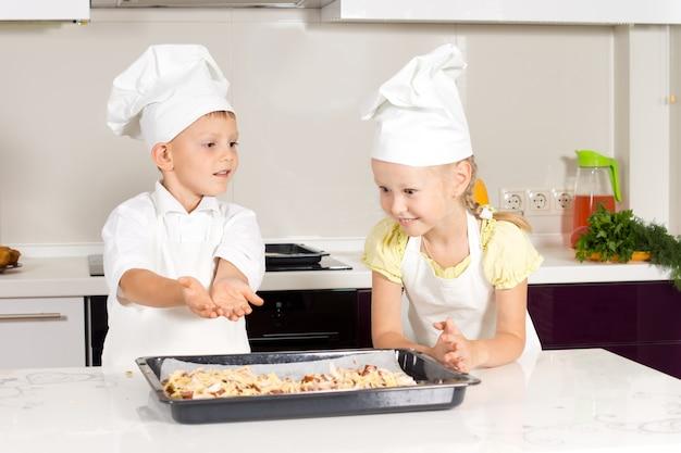 Mały chłopiec dodaje przyprawy do domowej pizzy