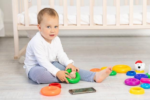 Mały chłopiec dwuletni bawiący się w pobliżu łóżeczka