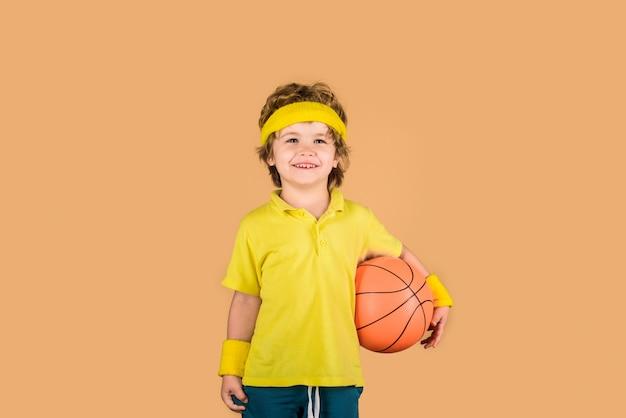 Mały chłopiec dziecko koszykarza w stroju sportowym trzyma piłkę koszykarz z piłką ładny chłopiec trzyma