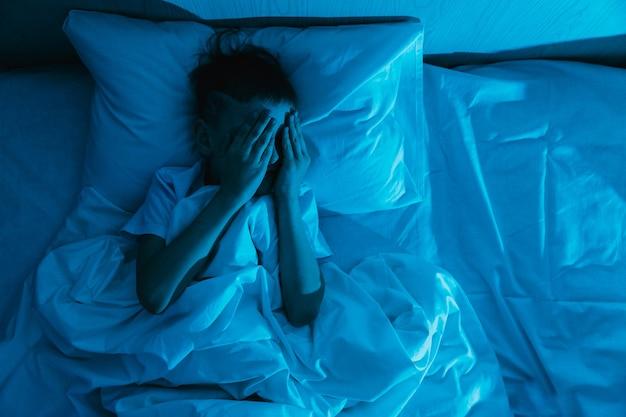 Mały chłopiec dziecko leży w łóżku w ciemną noc i zakrywa twarz rękami ze strachu, bojąc się koszmarów i strasznych snów u dzieci
