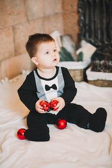 Mały chłopiec dziecko siedzi obok ozdobionej choinki z prezentami i prezentami