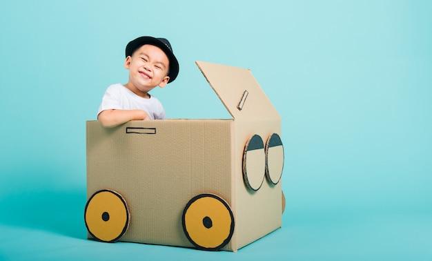 Mały chłopiec dziecko uśmiech w prowadzeniu samochodu kreatywnego przez karton