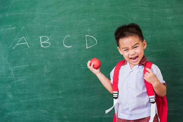 Mały chłopiec dziecko z przedszkola w mundurku studenckim z tornister trzymać czerwone jabłko