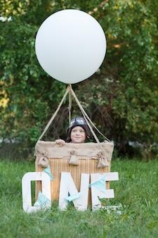Mały chłopiec flier w koszu z balonem