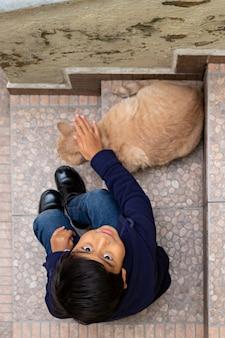 Mały chłopiec głaszczący żółtego kota po południu na podwórku domu