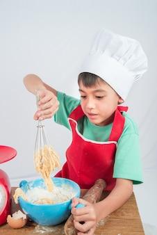 Mały chłopiec gotowanie ciasta domowej piekarni